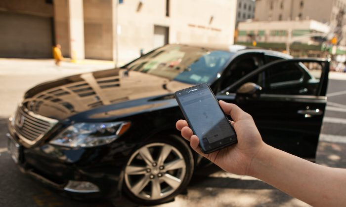 A person holds out his smartphone displaying the Uber app, before getting in a black Lexus which was hailed using the app, in Manhattan, on June 8, 2014. (Benjamin Chasteen/Epoch Times)