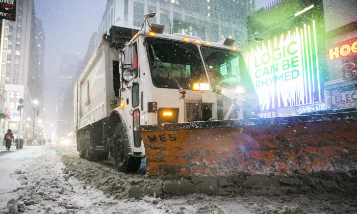 Trucks with snow plows drive down 7th Ave. during a blizzard in Midtown Manhattan on Jan. 26, 2015. (Samira Bouaou/Epoch Times)