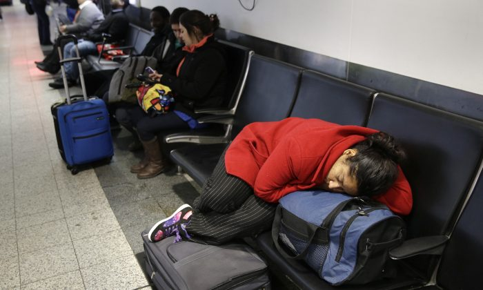 A woman sleeps on top of her luggage at LaGuardia Airport in New York, Monday, Jan. 26, 2015. Airlines canceled thousands of flights into and out of East Coast airports as a major snowstorm packing up to 3 feet of snow barrels down on the region.  (AP Photo/Seth Wenig)