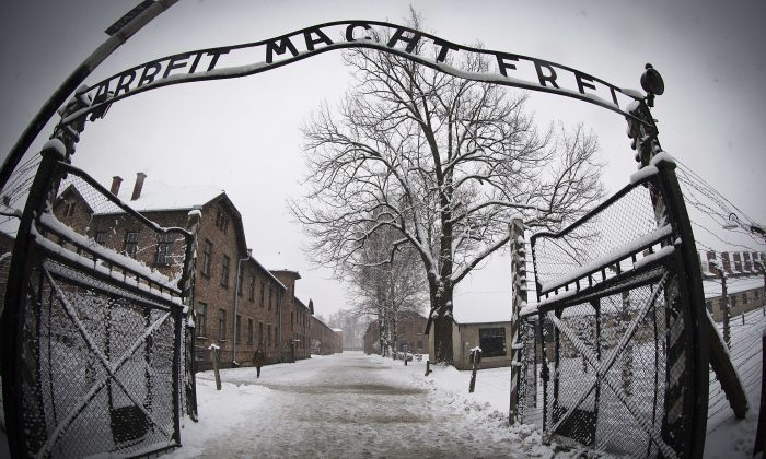 A woman walks through snow near the entrance to the former Nazi concentration camp Auschwitz-Birkenau with the lettering 'Arbeit macht frei' ('Work makes you free') in Oswiecim, Poland, on Jan. 25, 2015. (Joel Saget/AFP/Getty Images)