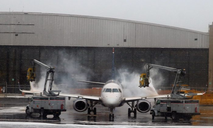 A US Airways jet is de-iced prior to takeoff at Laguardia Airport on January 26, 2015 in New York City. (Photo by Bruce Bennett/Getty Images)