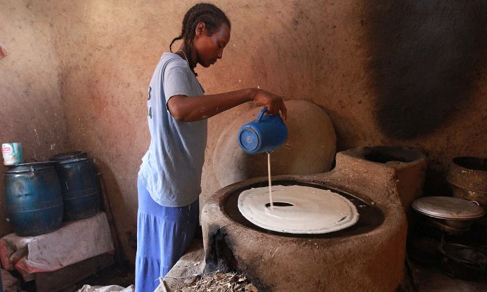 A young Ethiopian woman makes injera, a fermented bread made from the world's smallest grain. (SOLAN GEMECHU/AFP/Getty Images)