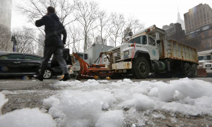"""A man crosses Sixth Ave., in front of New York City Sanitation trucks with snow plows attached, near Bryant Park in New York, Monday, Jan. 26, 2015. Officials cautioned Northeast residents to not be misled by a relatively smooth Monday morning commute, and pressed their cautions to prepare for a """"crippling and potentially historic"""" storm that could bury communities from northern New Jersey to southern Maine in up to 2 feet of snow starting later in the day. (AP Photo/Richard Drew)"""