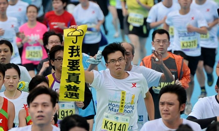 "A marathon runner holds up a Lion Rock ""I want genuine universal suffrage banner"" during the 2015 Hong Kong Marathon on Jan. 25, 2015. (Sung Cheung-loong/Epoch Times)"