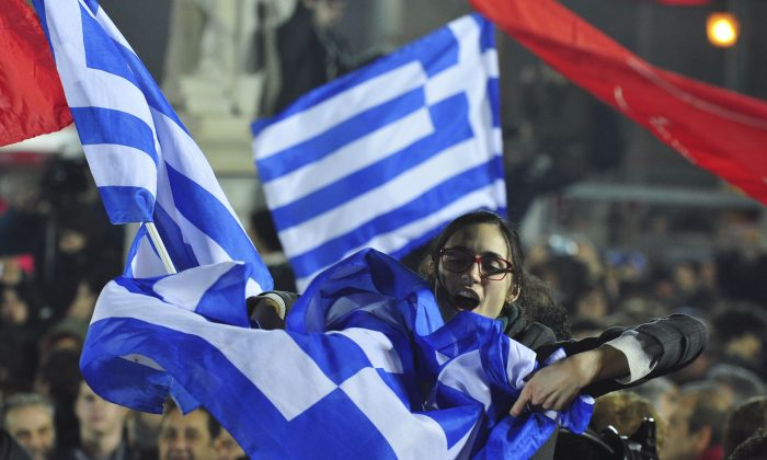 """A woman waves a Greek flag during a speech by the leader of Syriza left-wing party Alexis Tsipras outside Athens University Headquarters, Sunday, Jan. 25, 2015. A triumphant Alexis Tsipras told Greeks that his radical left Syriza party's win in Sunday's early general election meant an end to austerity and humiliation and that the country's regular and often fraught debt inspections were a thing of the past. """"Today the Greek people have made history. Hope has made history,"""" Tsipras said in his victory speech at a conference hall in central Athens. (AP Photo/Fotis Plegas G.)"""