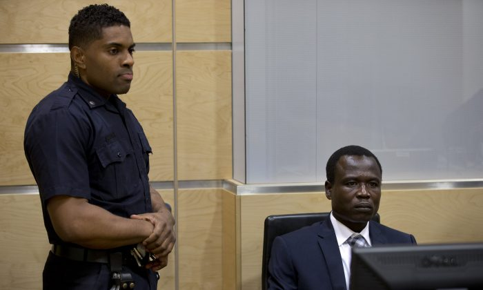 Dominic Ongwen, right, a Ugandan commander in warlord Joseph Kony's feared militia, waits for the start of court procedures as he made his first appearance at the International Criminal Court in The Hague, Netherlands, Monday, Jan. 26, 2015. Ongwen arrived in The Hague last week after being taken into custody in Central African Republic. He faces war crimes and crimes against humanity charges for his alleged role in a reign of terror that has spanned more than 25 years in central Africa's Great Lakes region. (AP Photo/Peter Dejong, Pool)