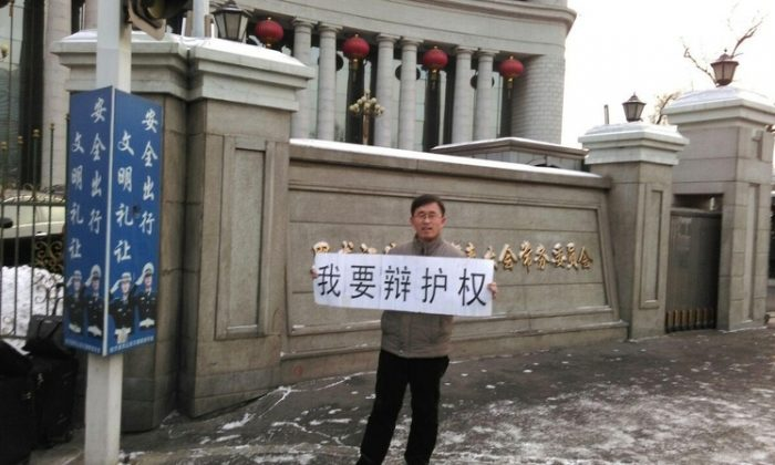 "Chinese lawyer Zhang Weiyu holds banner saying: ""I want to defend rights,"" in front of the Heilongjiang provincial government on Jan. 20. The president of the Supreme People's Court in China has recently told judges to stop expelling lawyers from the court room. (Epoch Times)"