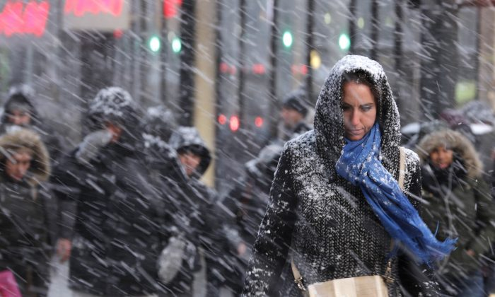 Pedestrians make their way through snow in New York, Monday, Jan. 26, 2015. (AP Photo/Seth Wenig)