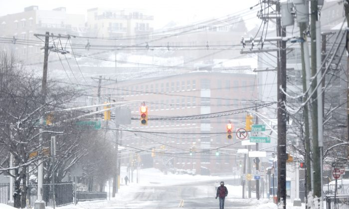 A pedestrian walks on a snow covered road after an overnight snowstorm, Tuesday, Jan. 27, 2015, in Hoboken, N.J. (AP Photo/Julio Cortez)