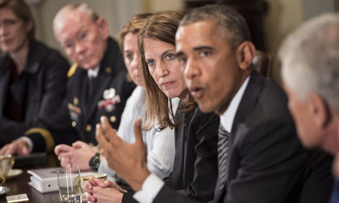 In this file photo, Sylvia Burwell (3R), Secretary of the Department of Health and Human Services, listens as US President Barack Obama (2R) makes a statement for the press after a meeting in the Cabinet Room of the White House October 15, 2014 in Washington, DC. (Brendan Smialowski/AFP/Getty Images)