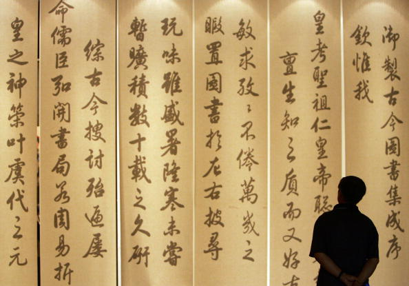 A visitor views ancient Chinese calligraphy works at the Wuying Palace of the Forbidden City on Aug. 27, 2005, in Beijing, China. Many corrupt Chinese officials are making enormous money by selling their own calligraphy works. (China Photos/Getty Images)