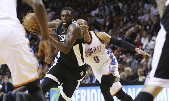 Oklahoma City Thunder's Russell Westbrook (0) tries to steal the ball from Miami Heat's Luol Deng during the first half of an NBA basketball game in Miami, Tuesday, Jan. 20, 2015. (AP Photo/J Pat Carter)