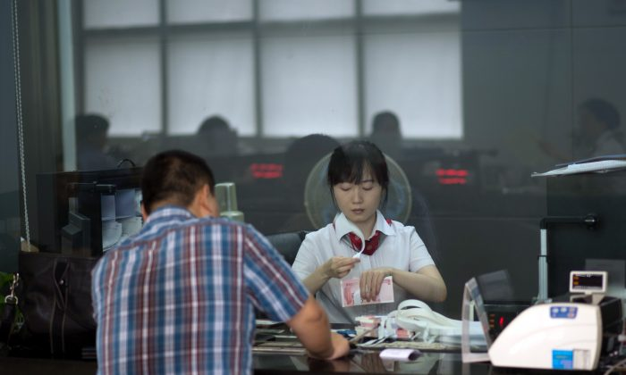 A worker of an Industrial and Commercial Bank of China Ltd (ICBC) branch counts money as she serves a customer in Shanghai on Sept. 24, 2014. (JOHANNES EISELE/AFP/Getty Images)