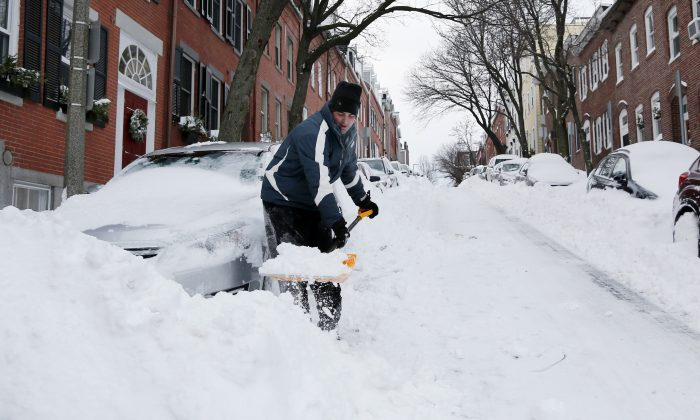 John Kenneally shovels his car out at his home in Boston's Charlestown section, Wednesday, Jan. 28, 2015, one day after a blizzard dumped about 2 feet of snow in the city. (AP Photo/Elise Amendola)