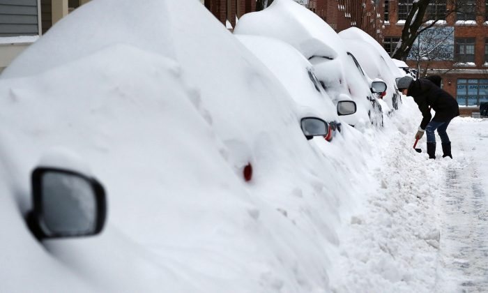 Jill Leach shovels her car out at her home in Boston's Charlestown section, Wednesday, Jan. 28, 2015, one day after a blizzard dumped about 2 feet of snow in the city. (AP Photo/Elise Amendola)