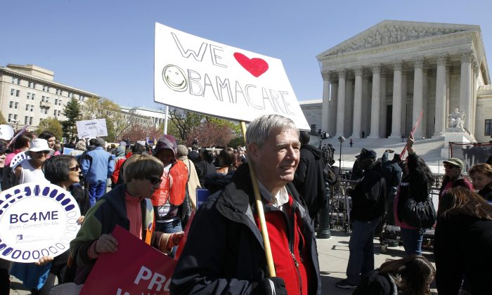 Supports of Obamacare rally in front of the Supreme Court before it ruled in favor of the individual mandate in Washington DC on March 27, 2012 (AP Photo/Charles Dharapak)