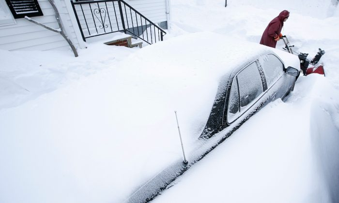 Phil Curran, 71, uses a snowblower to dig out a car that was buried in a snowdrift after a winter storm, Wednesday, Jan 28, 2015, in Portland, Maine. Tuesday's blizzard dumped about two feet of snow in Portland. (AP Photo/Robert F. Bukaty)