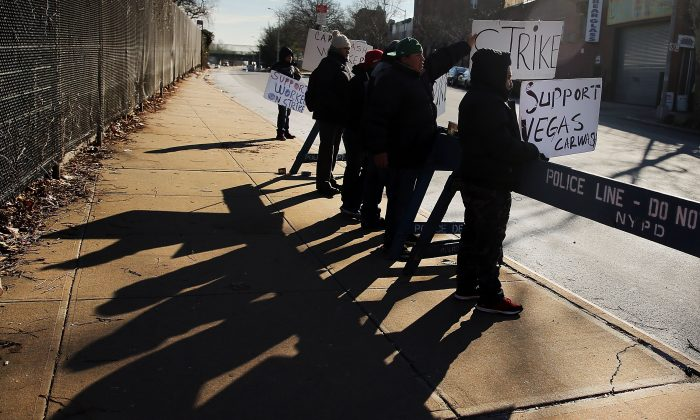 Workers from the Vegas Auto Spa stand on a picket line in front of the Brooklyn car wash in New York on Jan. 20, 2015. (Spencer Platt/Getty Images)