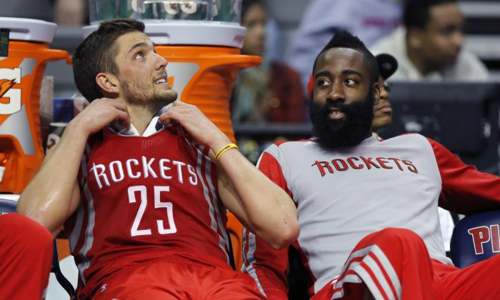 Houston Rockets forward Chandler Parsons (25) and guard James Harden (13) sit on the bench during the second half of an NBA basketball game against the Detroit Pistons Saturday, Dec. 21, 2013, in Auburn Hills, Mich. (AP Photo/Duane Burleson)