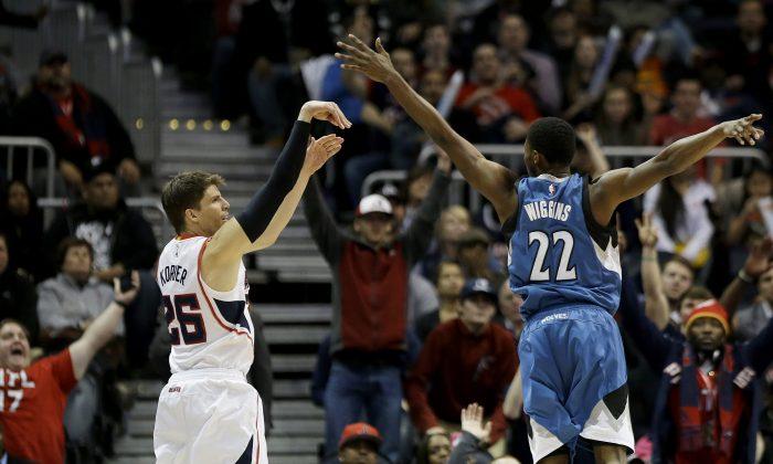 Atlanta Hawks' Kyle Korver, left, hits a three-point basket over Minnesota Timberwolves' Andrew Wiggins in the final minutes of an NBA basketball game, Sunday, Jan. 25, 2015, in Atlanta. (AP Photo/David Goldman)
