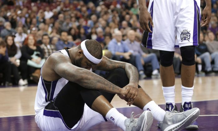 In this Jan. 21, 2015, file photo, Sacramento Kings center DeMarcus Cousins sits on the court after going to the floor in a scramble for the ball during the fourth quarter of an NBA basketball game against the Brooklyn Nets in Sacramento, Calif. (AP Photo/Rich Pedroncelli, File)