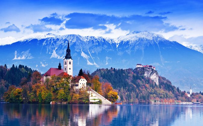 Lake and castle with mountains in background, Slovenia via Shutterstock*