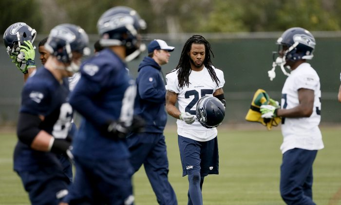 Seattle Seahawks' Richard Sherman puts his helmet on during a team practice for NFL Super Bowl XLIX football game, Thursday, Jan. 29, 2015, in Tempe, Ariz. The Seahawks play the New England Patriots in Super Bowl XLIX on Sunday, Feb. 1, 2015. (AP Photo/Matt York)