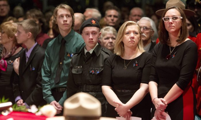 RCMP Constable David Wynn's sons (L-R) Alexander Wynn, Nathan Wynn, Matthew Wynn; wife Shelly MacInnis-Wynn; and sister Lindsay Sarty stand in front of David Wynn's casket during the funeral procession for the slain RCMP officer in St. Albert, Alta., on Jan. 26, 2015. (The Canadian Press/Jason Franson)