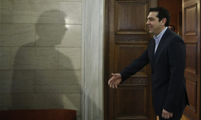 The shadow of Eurogroup chairman Jeroen Dijsselbloem is cast on a wall as Greek Prime Minister Alexis Tsipras waits to greets him during their meeting in Athens, Friday, Jan. 30, 2015.  (AP Photo/Petros Giannakouris, Pool)