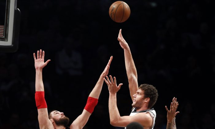 Brooklyn Nets' Brook Lopez, center, shoots against Toronto Raptors' Jonas Valanciunas (17), of Lithuania, during the second quarter of an NBA basketball game Friday, Jan. 30, 2015, in New York. (AP Photo/Jason DeCrow)
