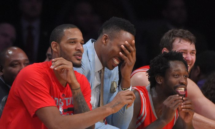 Houston Rockets' Trevor Ariza, left, Dwight Howard, center, and Patrick Beverley joke toward the the players on the court during the second half of an NBA basketball game Los Angeles Lakers, Sunday, Jan. 25, 2015, in Los Angeles.   The Lakers won 99-87. (AP Photo/Mark J. Terrill)
