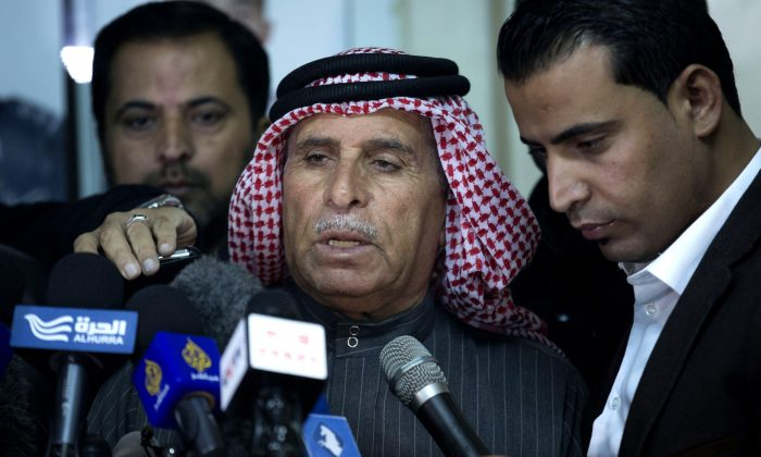 Safi al-Kaseasbeh, center, father of Jordanian pilot, Lt. Muath al-Kaseasbeh, who is held by the Islamic State group militants, reads a statement for the media urging his son's captors to have mercy on a fellow Muslim and spare his life, at the captured pilot's tribal gathering divan, in Amman, Jordan, Thursday, Jan. 29, 2015. (AP Photo/Nasser Nasser)