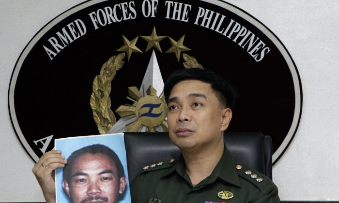 In this Feb. 2, 2012 file photo, then Armed Forces of the Philippines spokesman Col. Marcelo Burgos shows a picture of Malaysian Zulkifli bin Hir, also known as Marwan, during a press conference in suburban Quezon City, north of Manila, Philippines. (AP Photo/Pat Roque, File)
