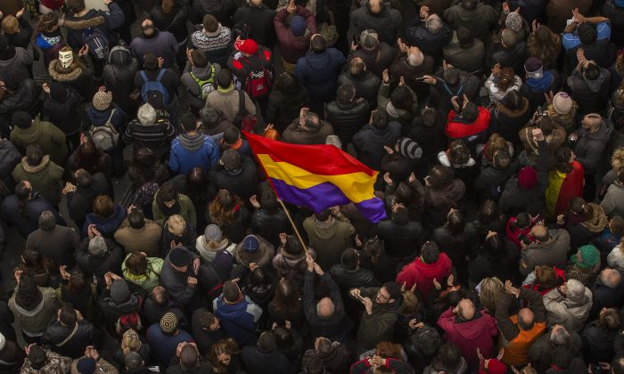 A man waves a Republican flag as people gather in the main square of Madrid during a Podemos (We Can) party march in Madrid, Spain, Saturday, Jan. 31, 2015. Tens of thousands of people  possibly more are marching through Madrid's streets in a powerful show of strength by Spain's fledgling radical leftist party Podemos (We Can) which hopes to emulate the electoral success of Greece's Syriza party in elections later this year. (AP Photo/Andres Kudacki)