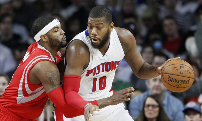 Detroit Pistons' Greg Monroe (10) drives against Houston Rockets' Josh Smith (5) during the first half of an NBA basketball game Saturday, Jan. 31, 2015, in Auburn Hills, Mich. (AP Photo/Duane Burleson)