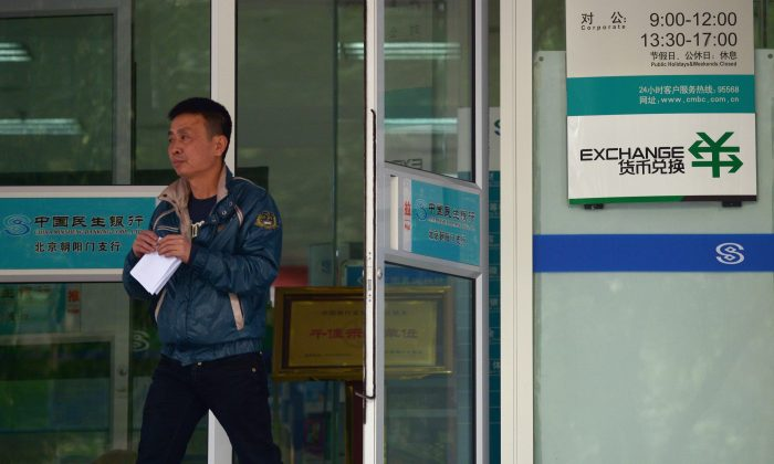 In this file photo, a man walks out of a bank in Beijing on October 31, 2013. New rules will require foreign technology companies that serve banks in Beijing to provide their source code and put backdoors in their software. (Wang Zhao/AFP/Getty Images)