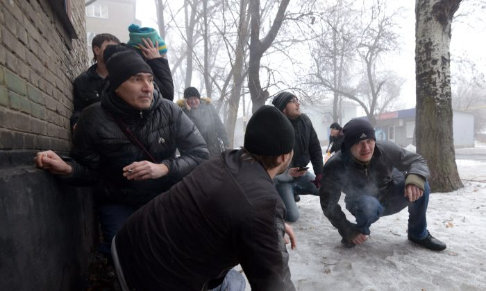 People take cover during a shelling in a residential area in Donetsk's Kyibishevsky district, Ukraine, on Jan. 30, 2015. (Dominique Faget/AFP/Getty Images)
