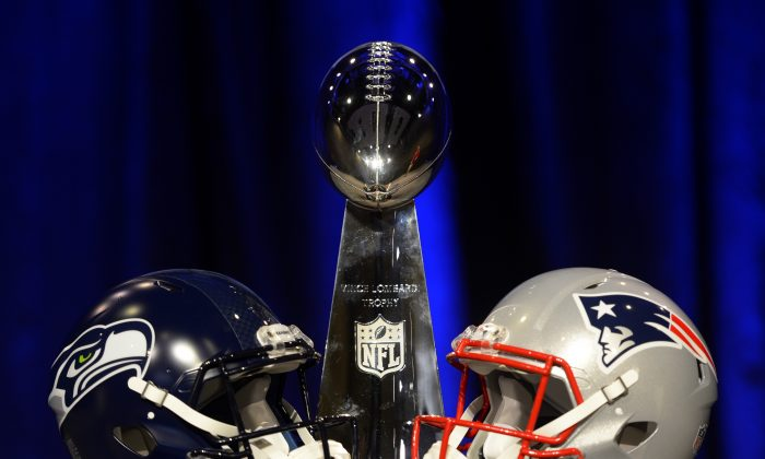 The Vince Lombardi Trophy sits alongside the helmets of the Seattle Seahawks (L) and New England Patriots before a press conference of the coaches of Super Bowl XLIX at the Phoenix Convention Center in Phoenix, Ariz., on Jan. 30, 2015. (Timothy A. Clary/AFP/Getty Images)