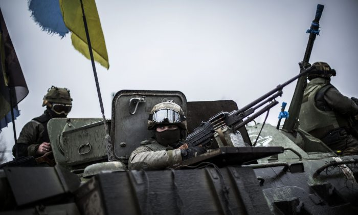 Ukrainian soldiers are seen in an armoured vehicle topped with a Ukrainian flag near the city of Artemivsk, in the Donetsk region, before heading to the city of Debaltseve about 45 km away, on Feb. 1, 2015. (Manu Brabo/AFP/Getty Images)