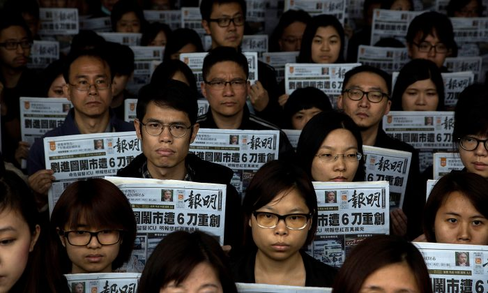 Staff members of Ming Pao hold a tribute for former chief editor Kevin Lau, who was stabbed, outside the Ming Pao office on Feb. 27, 2014 in Hong Kong. (Lam Yik Fei/Getty Images)