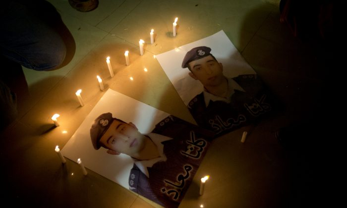 """Members of Al-Kaseasbeh, the tribe of Jordanian pilot, Lt. Muath al-Kaseasbeh, who is was murdered by the Islamic State group militants, light candles by posters with his picture and Arabic that reads """"we are all Muath."""" (AP Photo/Nasser Nasser)"""