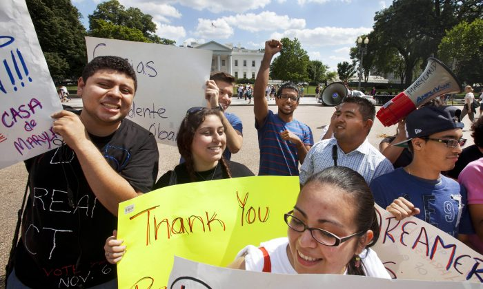 """In this June 15, 2012 file photo, Ricky Campos, 23, of Silver Spring, Md., left, Katye Hernandez, 22, both illegal immigrants originally from El Salvador, who live in Silver Spring, Md., hold signs saying """"Thank You President Obama"""" in Washington, D.C. The group Casa de Maryland, rallied outside the White House in Washington in support of the president's announcement that the U.S. government will stop deporting and begin granting work permits to younger illegal immigrants who were brought to the U.S. by their parents when they were children, known as """"Dreamers."""" Thousands of """"Dreamers"""" are deciding if they will apply for DACA, or deferred action program, costing $465 dollars. Due to the price, some may wait for comprehensive immigration reform that might grant them legal residency. (AP Photo/Jacquelyn Martin, File)"""