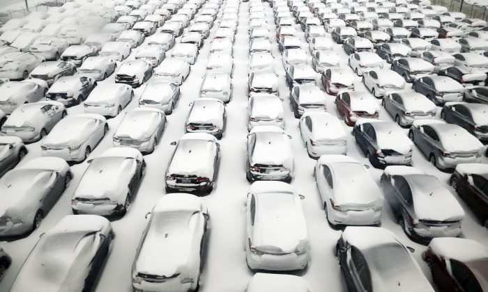 Cars are covered by snow in parking lot at O'Hare International Airport on Sunday, Feb. 1, 2015, in Chicago. The first major winter storm of the year is bearing down on the Chicago region, bringing with it blizzard conditions of heavy snow and strong winds. Numerous Chicago-area attractions are closed, more than 1,100 flights have been canceled at Chicago's airports and snow-covered roads are making travel treacherous. (AP Photo/Nam Y. Huh)