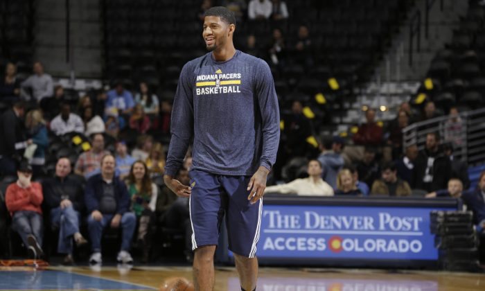 Injured Indiana Pacers guard Paul George jokes with teammates while shooting before facing the Denver Nuggets in an NBA basketball game Saturday, Dec. 20, 2014, in Denver. George has been sidelined since July when he fractured both his tibia and fibula during a Team USA basketball scrimmage in Las Vegas. (AP Photo/David Zalubowski)