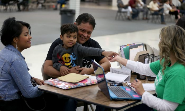 Mayra Pinto (L), Gino Alexander Bernate (C), 5, and Gino Bernate sit with Adriana Romero, an agent from Sunshine Life and Health Advisors, as they discuss plans available from the Affordable Care Act in Miami on Dec. 15, 2014. (Joe Raedle/Getty Images)