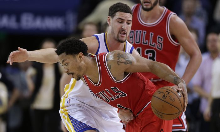 Chicago Bulls' Derrick Rose dribbles around Golden State Warriors' Klay Thompson during the second half of an NBA basketball game Tuesday, Jan. 27, 2015, in Oakland, Calif.  (AP Photo/Marcio Jose Sanchez)
