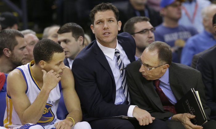 Golden State Warriors' Stephen Curry, left, talks with assistant coach Ron Adams, right, as assistant coach Luke Walton watches during the first half of an NBA basketball game against the Houston Rockets in Oakland, Calif., Wednesday, Jan. 21, 2015. (AP Photo/Jeff Chiu)