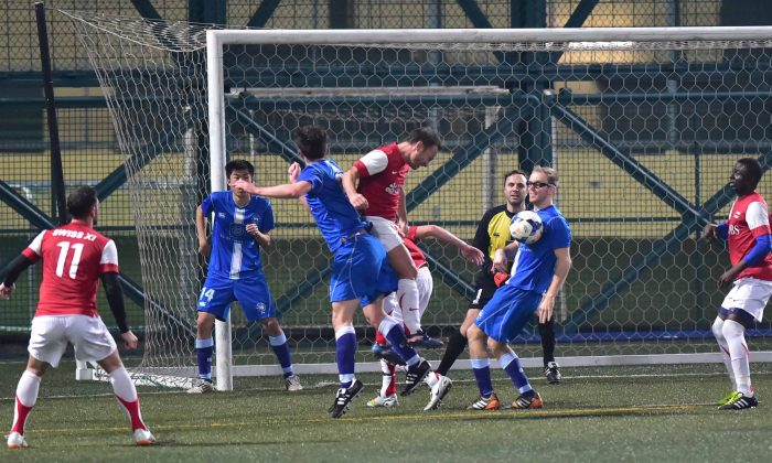 Robbie Bacon of Colts (blue kit) chests the ball to block a header from a Swiss XI corner in their Yau Yee League division one match at Hong Kong Football Club on Sunday Feb 1, 2015. Swiss XI won the match 2-1. (Bill Cox/Epoch Times)