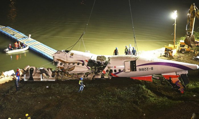 The mangled fuselage of a TransAsia Airways commercial plane is dragged to the river bank after it crashed in Taipei, Taiwan. The Taiwanese commercial flight with 58 people aboard clipped a bridge shortly after takeoff and crashed into a river in the island's capital of Taipei on Wednesday morning, Feb. 4, 2015. (AP Photo)
