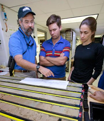 Penman (the lead author) offered this image of himself (center), Richard Norris (Scripps) and Pincelli Hull (Yale) inspecting sediment cores from the PETM while aboard a scientific drilling vessel. Photo credit Donald Penman.